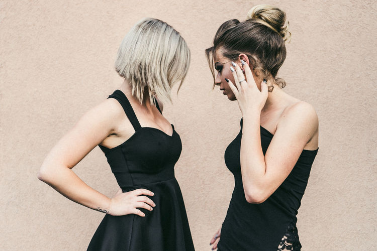 Side view of young women standing against wall
