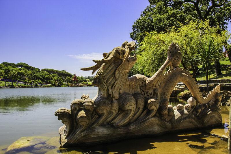 Dragon Dragon Sculpture Animal Animal Representation Bacalhoa Day Dragon Statue Lake No People Outdoors Park Representation Sculpture Statue Sunlight Tranquility Moments Water