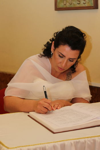 Bride writing in book while sitting at table during wedding ceremony