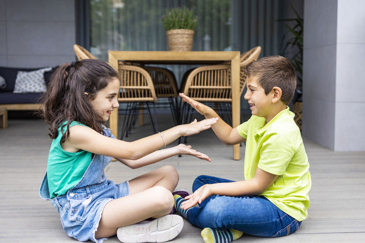 Two friends clapping hands at home