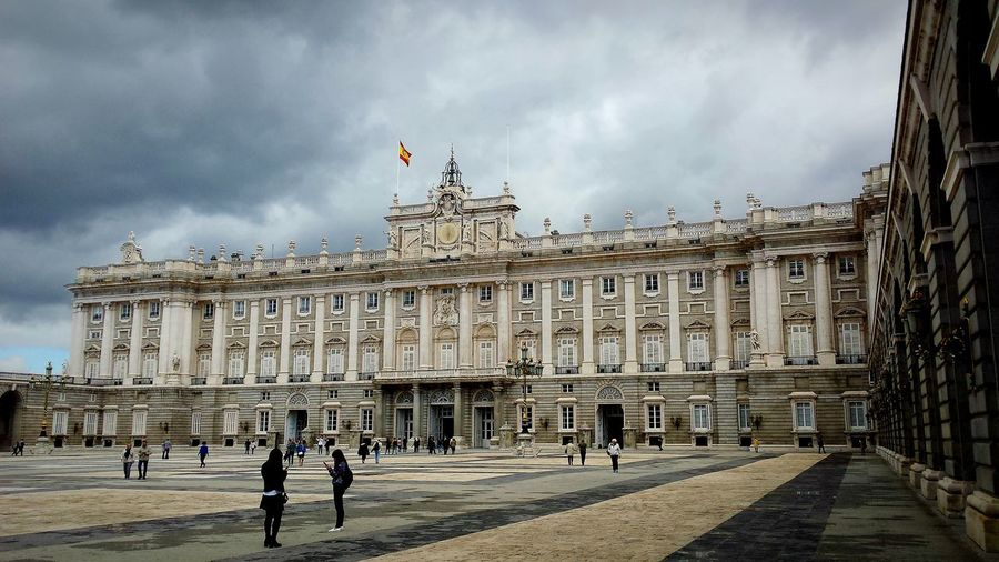 People outside royal palace of madrid in city