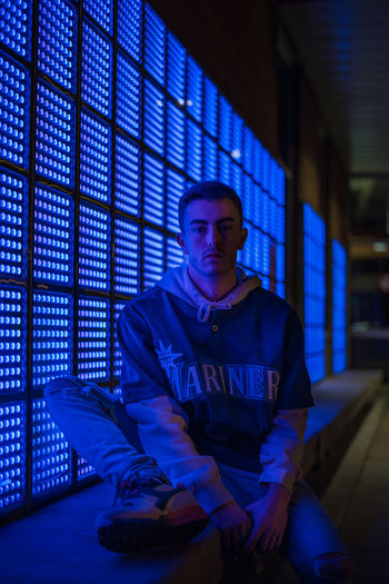 Portrait of serious young man sitting by illuminated building at night