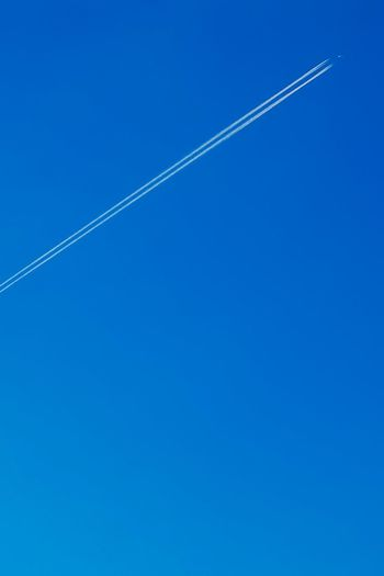 Sky Blue Vapor Trail Low Angle View Clear Sky Nature Copy Space No People Day Beauty In Nature Transportation Scenics - Nature Outdoors Tranquility Tranquil Scene Airplane Air Vehicle Mode Of Transportation Sunny Directly Below