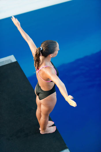 Female Diver On Platform, Preparing To Dive Swimming Diving Athlete Diving Board Individual Sports Water Sport Woman Above Blue Day Dive Female High Angle View Muscular Build One Person Outdoors Pool Preparation  Side View Sport Strength Swimming Pool Water Young Adult Young Women