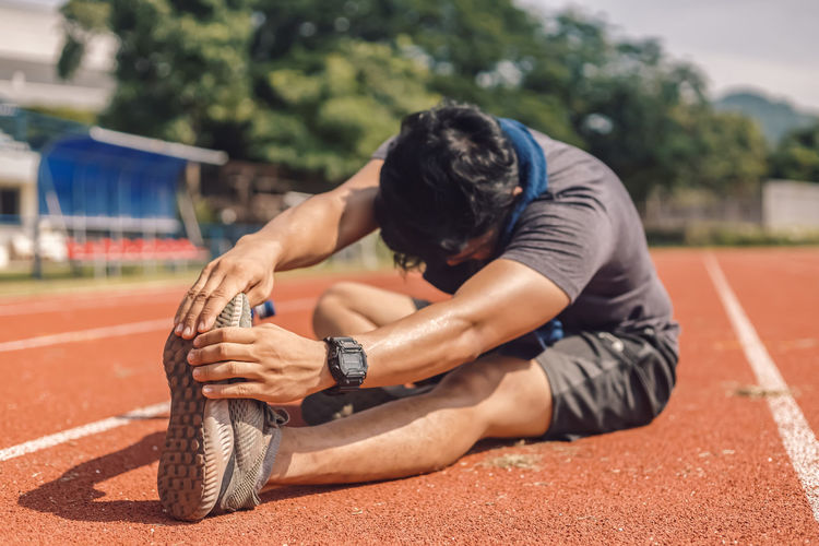 Full length of man exercising while sitting on sports track