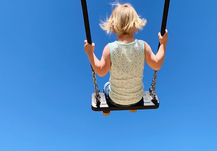 Rear view of girl swinging on swing against clear blue sky