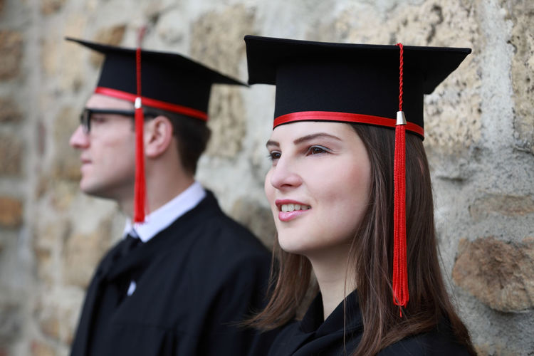 Couple wearing mortarboards standing by wall