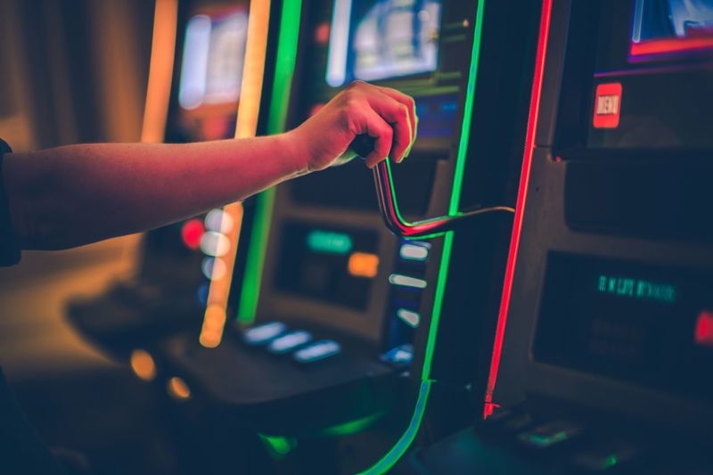 Cropped hand of boy playing games on slot machine