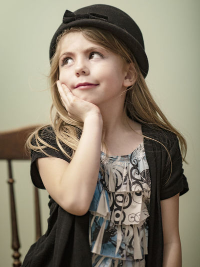 A seven-year-old girl sits for a natural light portrait in her home while wearing a hat. Young Adult Portrait Hat Young Women One Person Hair Front View Women Beauty Hairstyle Clothing Indoors  Beautiful Woman Casual Clothing Long Hair Leisure Activity Wall - Building Feature Looking At Camera Fashion Contemplation Hat