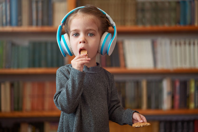 Cute girl wearing headphones in library