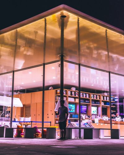 Reflection of man on glass window at night