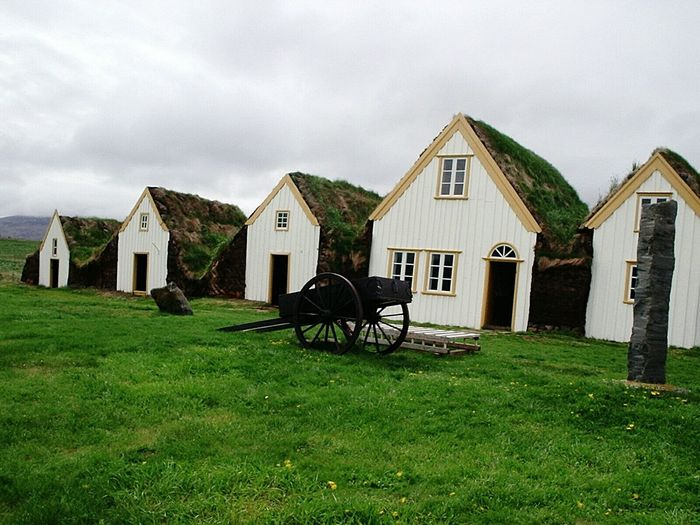 Turf-roofed farmhouses at folk museum against sky