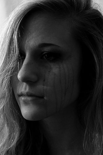 Close-up portrait of a beautiful young woman crying