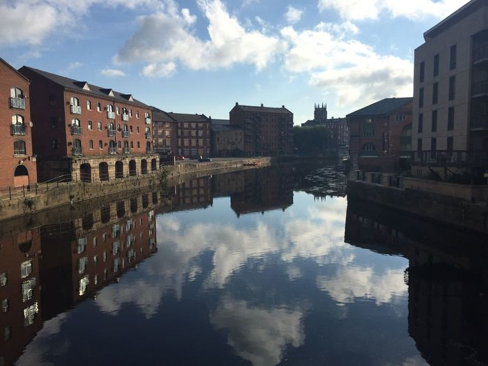 Reflection of sky on canal by buildings in city