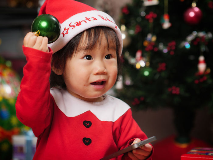 Cute girl wearing costume standing by christmas tree at home