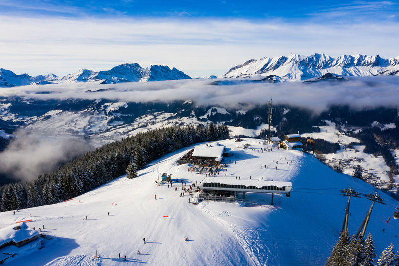 Aerial view of people skiing on snow covered mountain against sky