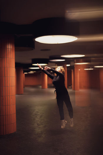 Woman jumping in illuminated garage