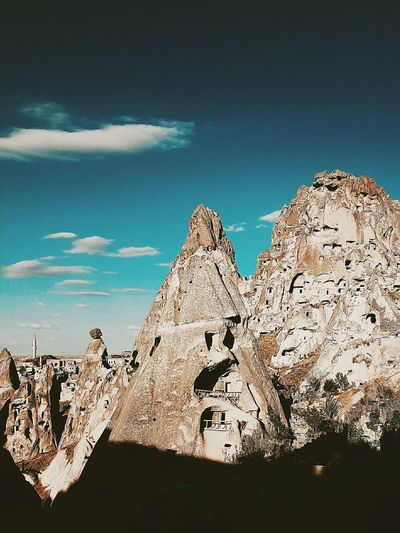 Scenic view of rock formation and buildings against sky
