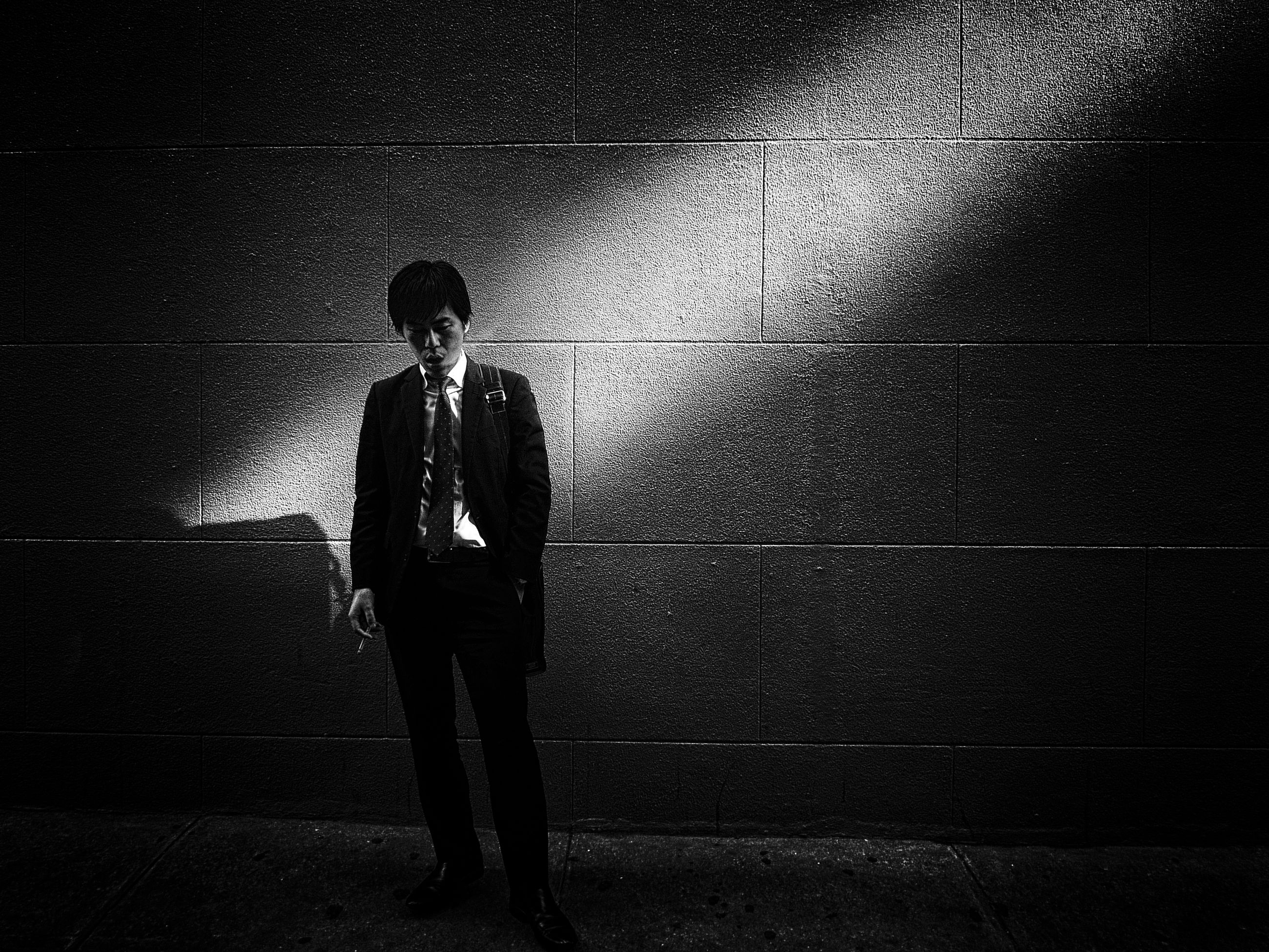 one person, real people, wall - building feature, standing, full length, lifestyles, men, leisure activity, front view, young adult, footpath, casual clothing, young men, night, shadow, architecture, dark, adult, teenager, depression - sadness, waiting
