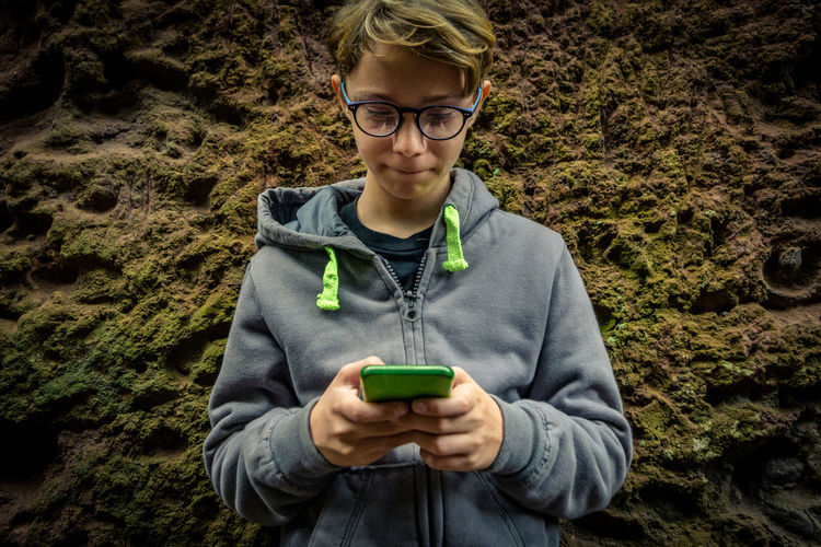 Smiling boy using mobile phone against rock