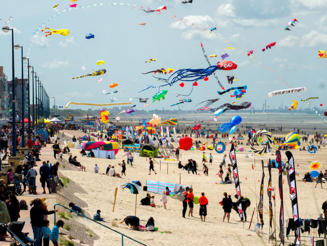 Beach Crowd Crowded Sky Day Enjoyment Festival Flying Flying In The Sky Fun Giant Kites Kites Large Group Of People Leisure Activity Lifestyles Mixed Age Range Nature Outdoors People Real People Sky Tied Vacations Windy Day