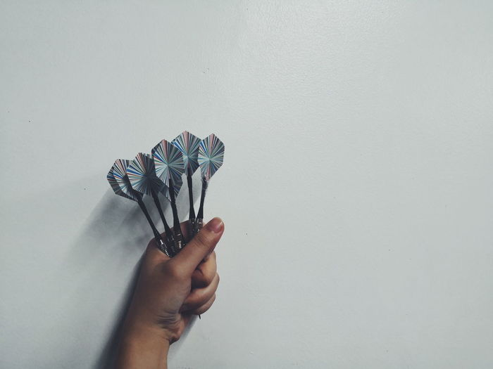 Close-up of hand holding darts against white background