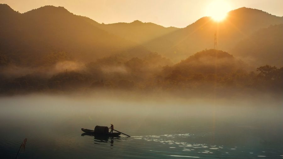 Silhouette man on boat in lake against mountains during sunset