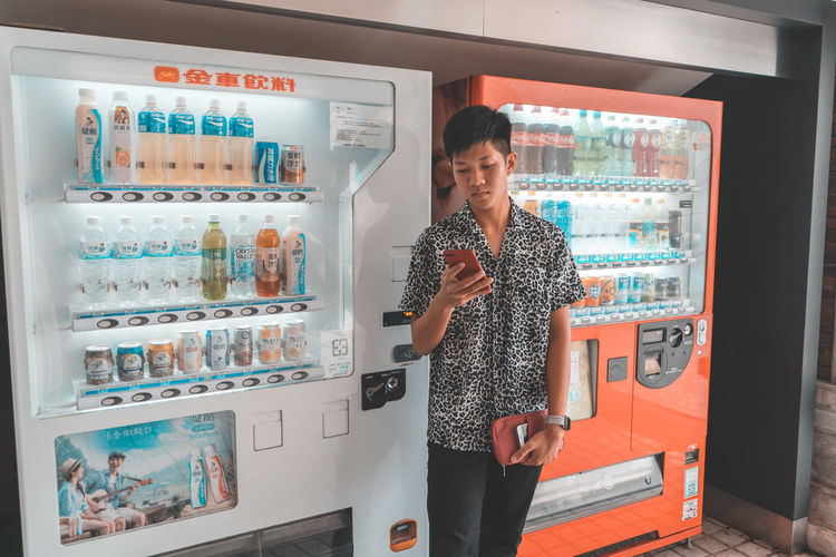 Standing One Person Three Quarter Length Indoors  Real People Lifestyles Front View Looking At Camera Technology Choice Casual Clothing Young Adult Store Adult Retail  Communication Refrigerator Portrait