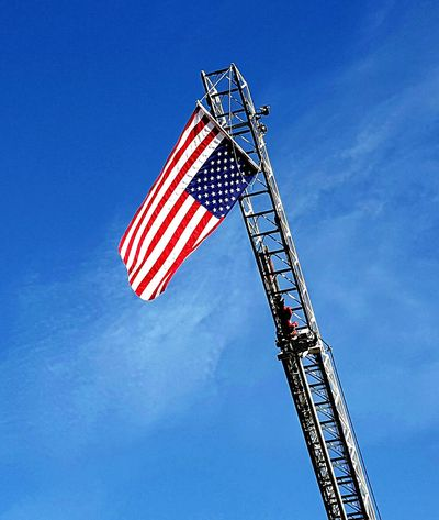 American flag hanging from the ladder of a Reno Fire Department fire truck on Veterans Day 2016 Flag Cultures Blue Low Angle View Patriotism Sky No People Clear Sky Day Outdoors Stars And Stripes American Flag Red White Blue 🇺🇸 Symbolism Hanging Firetrucks Ladder In Sky