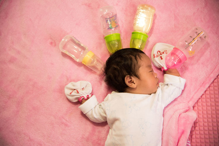 Directly above shot of baby sleeping on bed with milk bottles at home