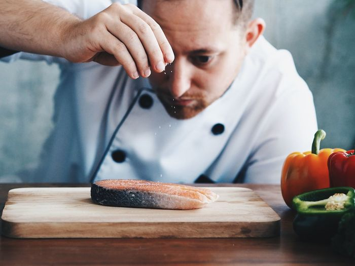 Close-Up Of Male Chef Seasoning Raw Fish On Table