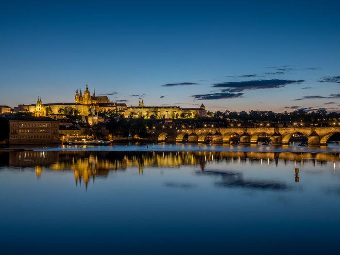 Illuminated prague castle by charles bridge over vltava river