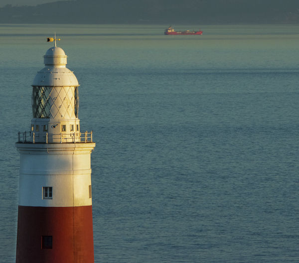 Lighthouse by sea against sea  and ship