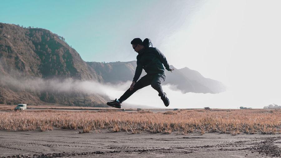 Full length of man jumping on field against sky