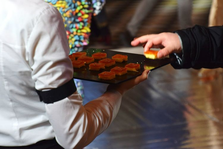 Midsection of woman serving food to man