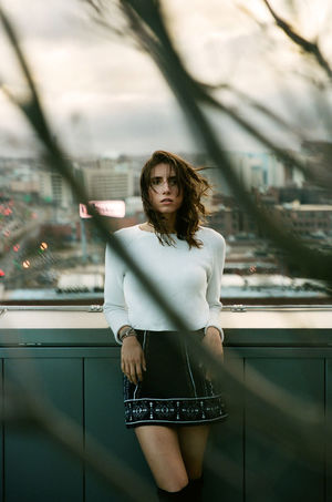 Branches Hair High Rise Portrait Of A Woman Roof Rooftop Architecture Beautiful Woman Day Fashion Front View Leisure Activity Lifestyles Looking At Camera Messy Hair One Person Outdoors Portrait Real People Skirt Skyskraper Standing Three Quarter Length Young Adult Young Women