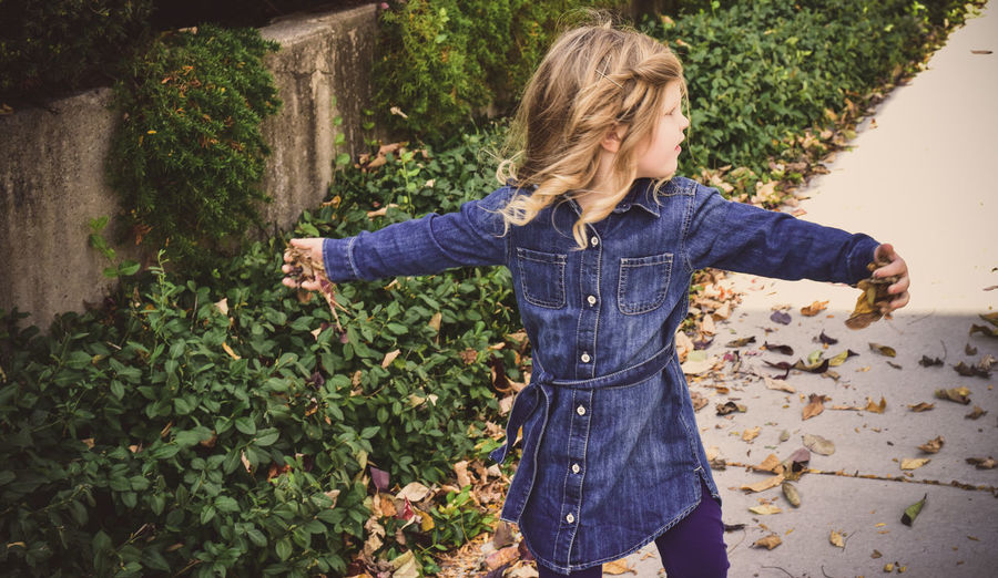 High Angle View Of Girl With Arms Outstretched Standing On Footpath