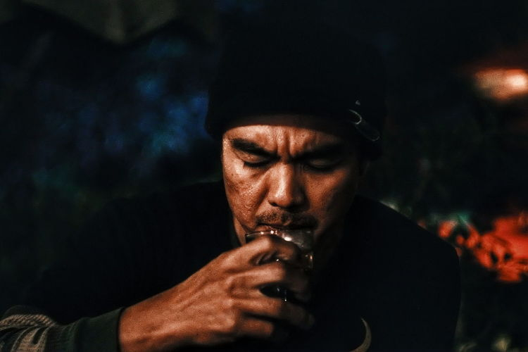 Close-Up Of Man Drinking At Night