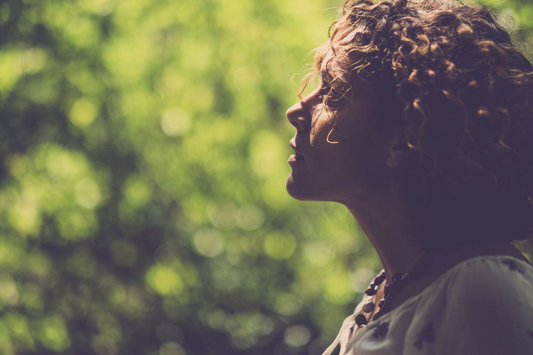 Alone woman looking outside Green Color Romantic Thinking Beauty Close-up Curly Hair Day Face Focus On Foreground Headshot Human Back Looking Nature One Person Outdoors People Real People Rear View Tree Women Young Women