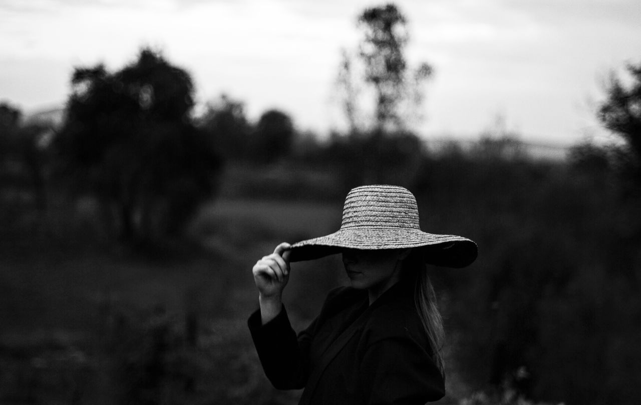 Woman holding hat while standing on field against sky
