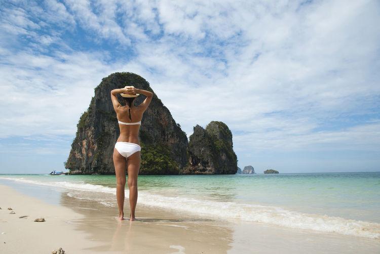 Rear view of sensuous woman wearing bikini at beach against sky