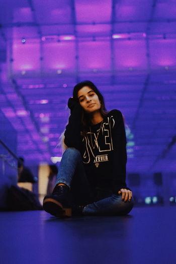 Portrait of beautiful young woman sitting on nightclub