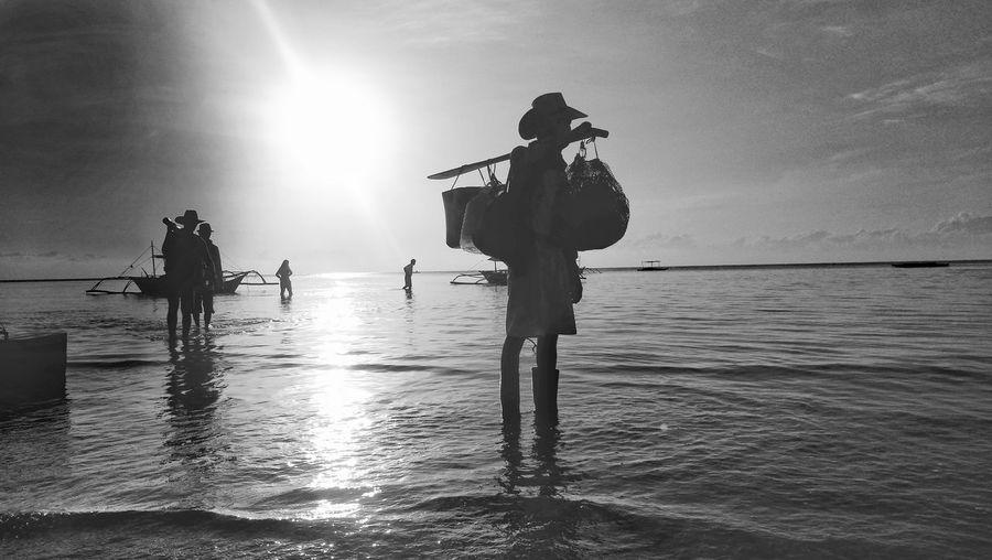 Silhouette people standing in sea against sky