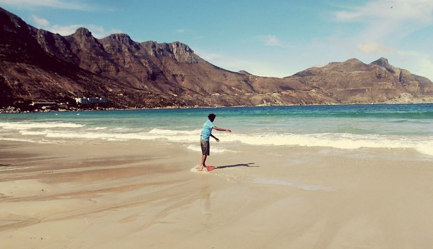 Skimboarding on Hout Bay beach. Beach Sea Sport Outdoors One Person Nature Sky Mountain Range South Africa Hout Bay Hout Bay Beach Cape Town Copy Space South Africa Is Amazing Travel Destinations