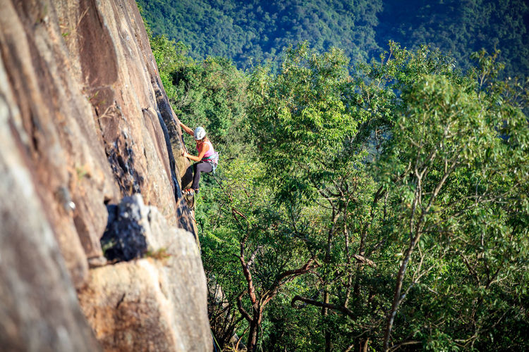 Woman Climbing On Rocky Mountain