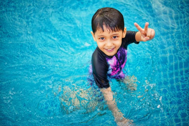 Portrait of smiling boy gesturing while standing in swimming pool