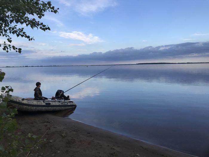 People fishing in lake against sky