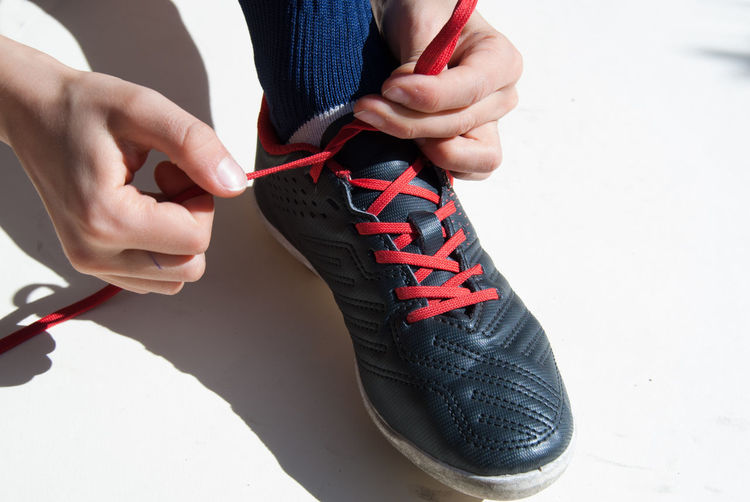 One Person Human Hand Human Body Part Real People Hand Shoe Holding Close-up Shoelace Body Part Lifestyles Leisure Activity Tying Women Low Section Day Red Adult Indoors  Child Sport Soccer Dressed Up