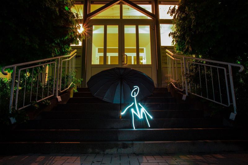 Light Painting By Umbrella Against House At Night