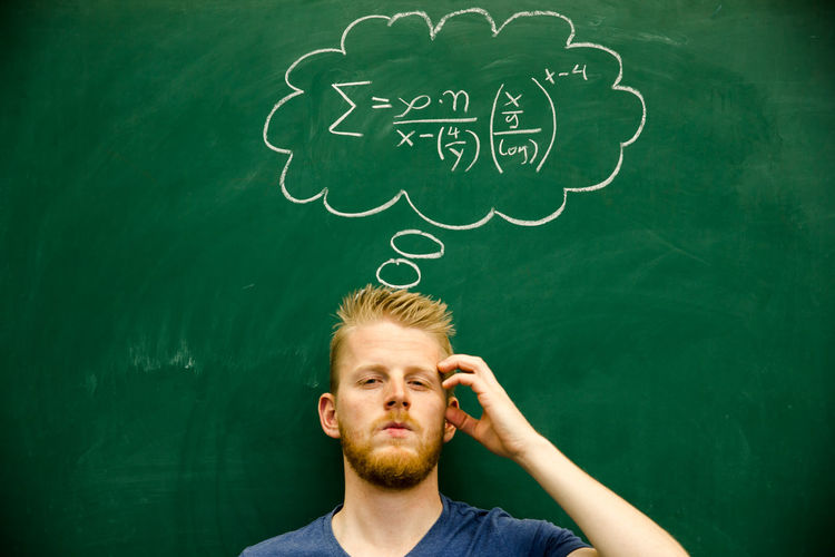 Man gesturing with mathematical formula on blackboard